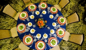 Blue Spark - Phoenician - Navy blue linen, orange chargers, orange centerpiece